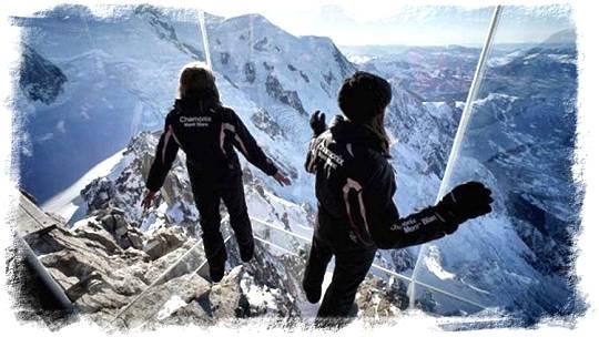 Blick ins Bodenlose: Auf einer gläsernen Brücke am Gipfel des Aiguille du Midi genießen zwei Mitarbeiterinnen der Seilbahngesellschaft den Blick auf die Region um den Montblanc